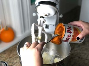 A can of pumpkin is added to a baked donut recipe.