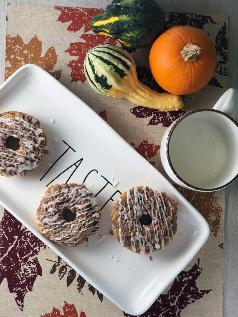 Three baked pumpkin streusel donuts arranged on a plate.