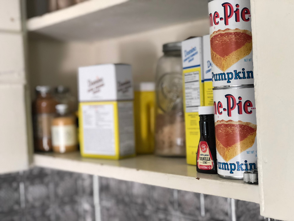 A cupboard in a butler's pantry with baking supplies on display.