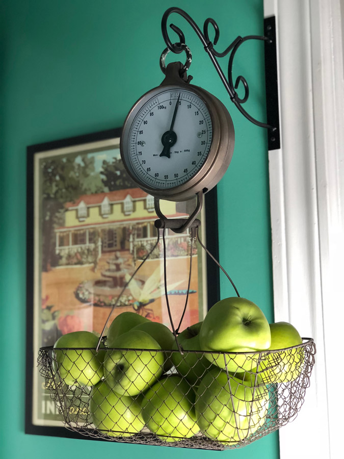 A butler's pantry that has been turned into a baking space, with apples on display on a scale.