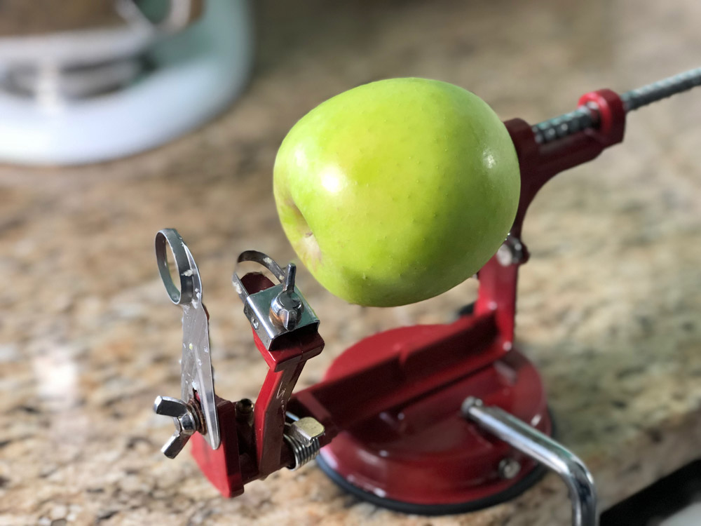 A green apple is placed on an apple peeler in preparation for a mini apple bundt cake recipe.