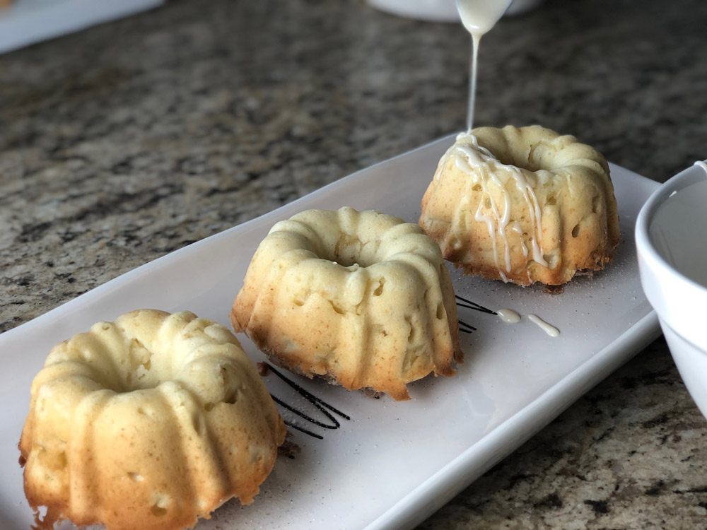 A baker adds maple icing to mini apple bundt cakes.