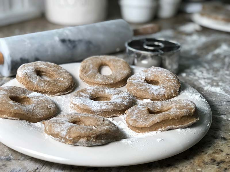 The cut apple cider donuts dough sits on a floured plate.