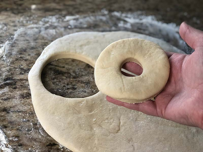 A baker displays what a donut looks like once it is cut.