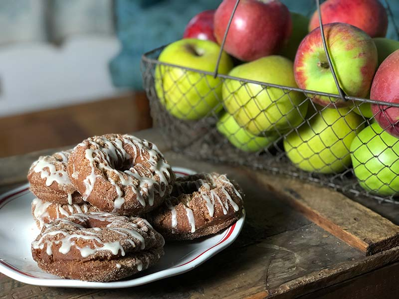 Fried apple cider donuts with maple glaze are displayed on a plate.