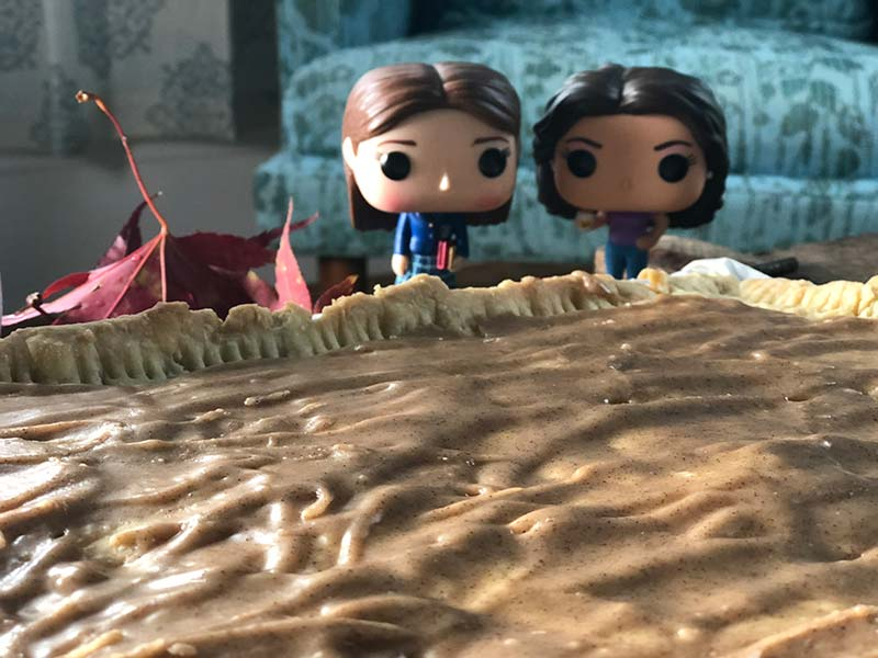 Two Gilmore Girls figurines are posed next to this giant homemade brown sugar cinnamon Pop-Tart.