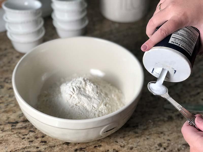 A baker measures salt for the apple cider donuts recipe.