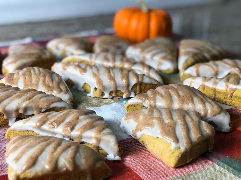 Over a dozen mini pumpkin spice scones, topped with icing, are on display.