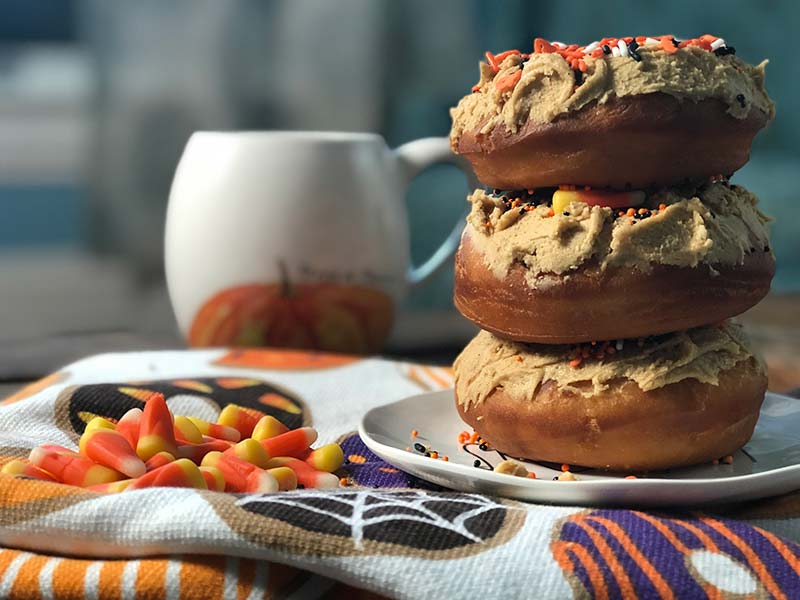Three pumpkin frosted donuts are stacked on top of each other.