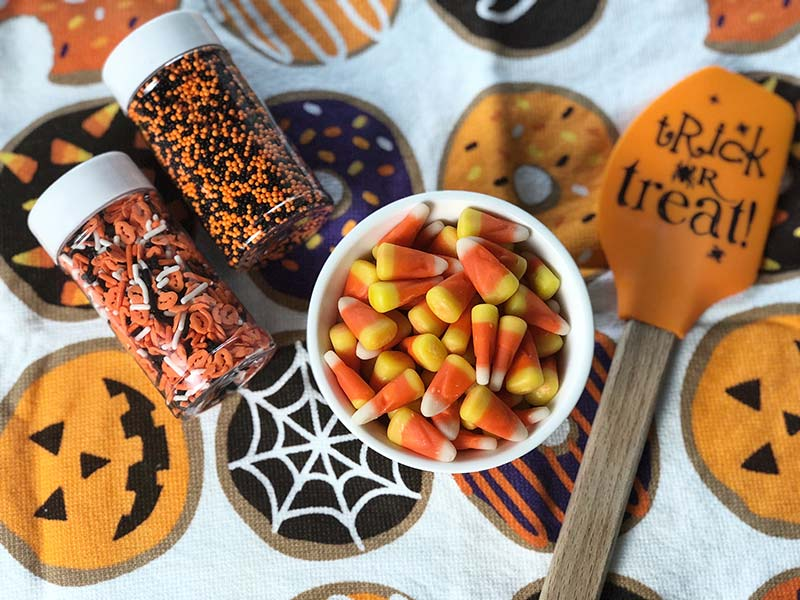 Candy corn and Halloween sprinkles are on display before being used as topping for pumpkin frosted donuts.