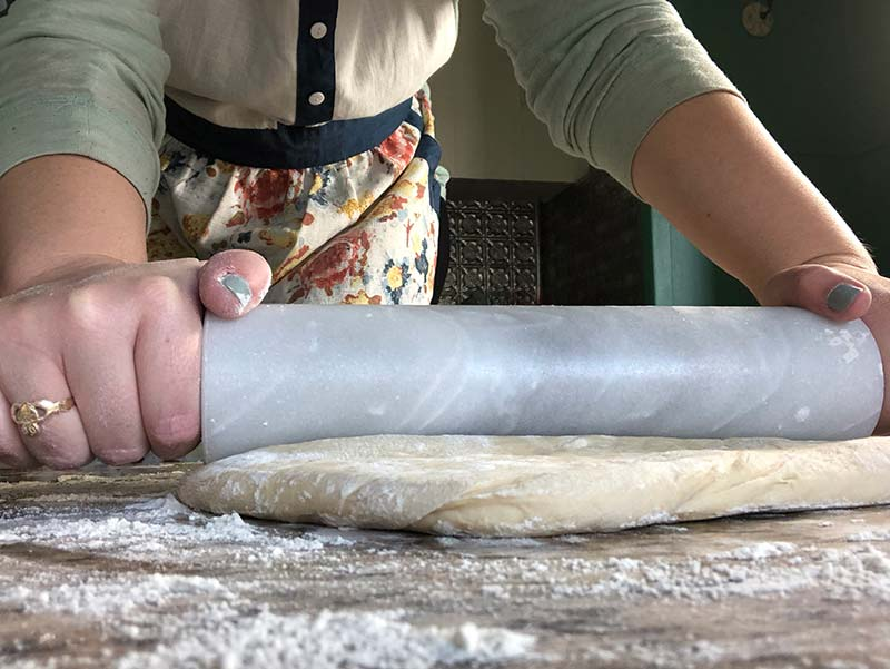 A baker rolls out doughnut dough for a delicious recipe.