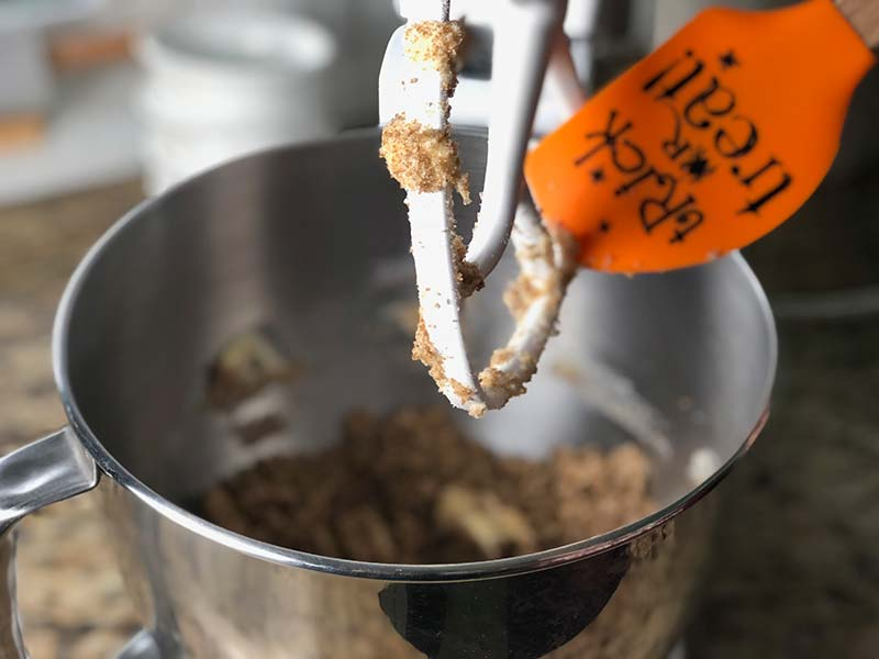 A baker scrapes the sugar mixture from a Kitchen Aid mixer for the apple cider donuts recipe.