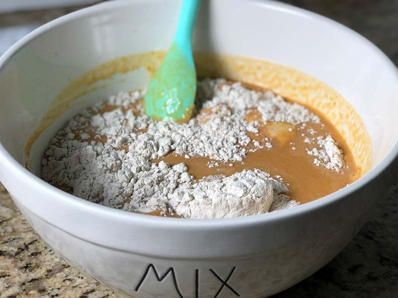 A baker mixes the dry and wet ingredients to form the pumpkin pancake batter.