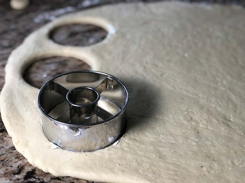 A donut cutter is used on the maple frosted donuts dough.