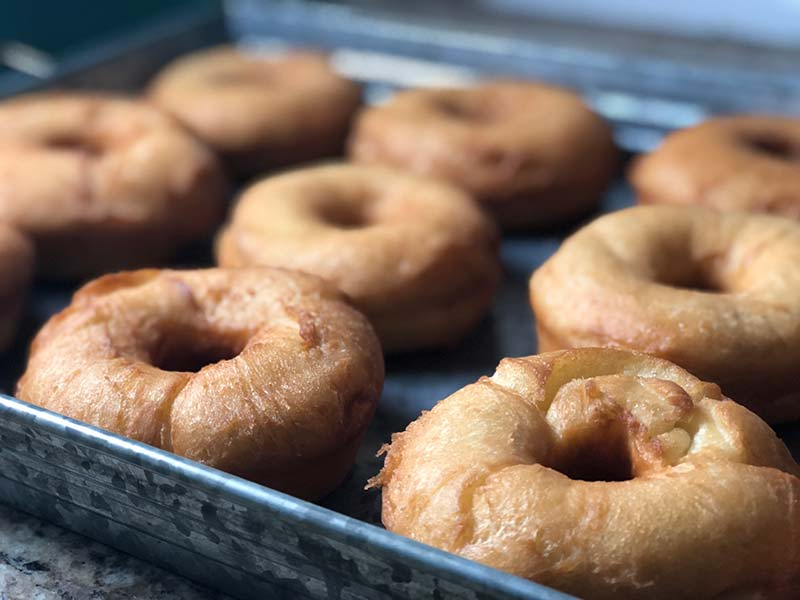 Freshly fried donuts are on display before being frosted.