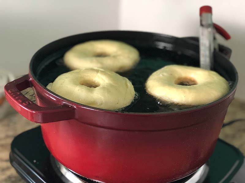 Donuts are frying in a dutch oven.