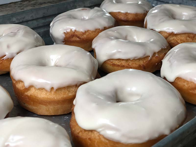 Donuts are on display after being dipped in maple frosting.