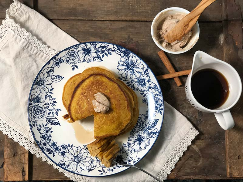 These pumpkin pancakes are topped with maple cinnamon butter and real maple syrup.