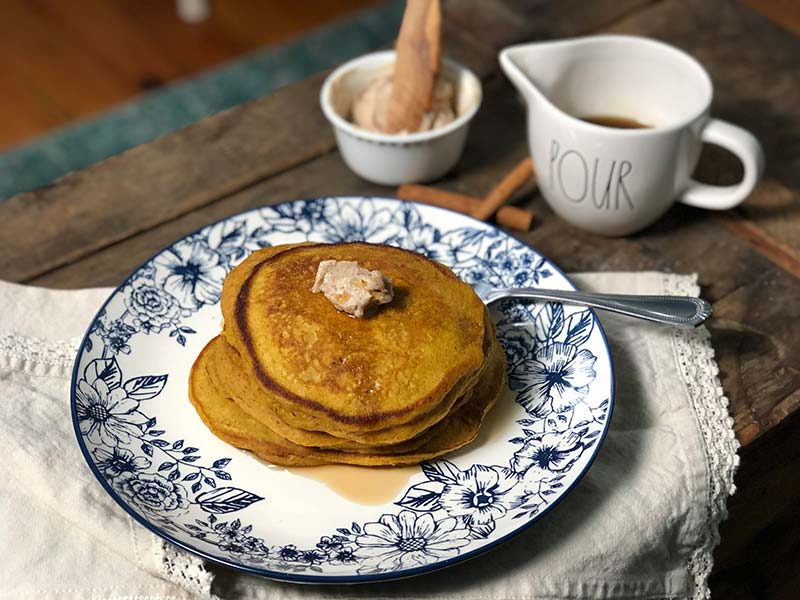A stack of pumpkin pancakes with maple cinnamon butter and real maple syrup sits on a plate.