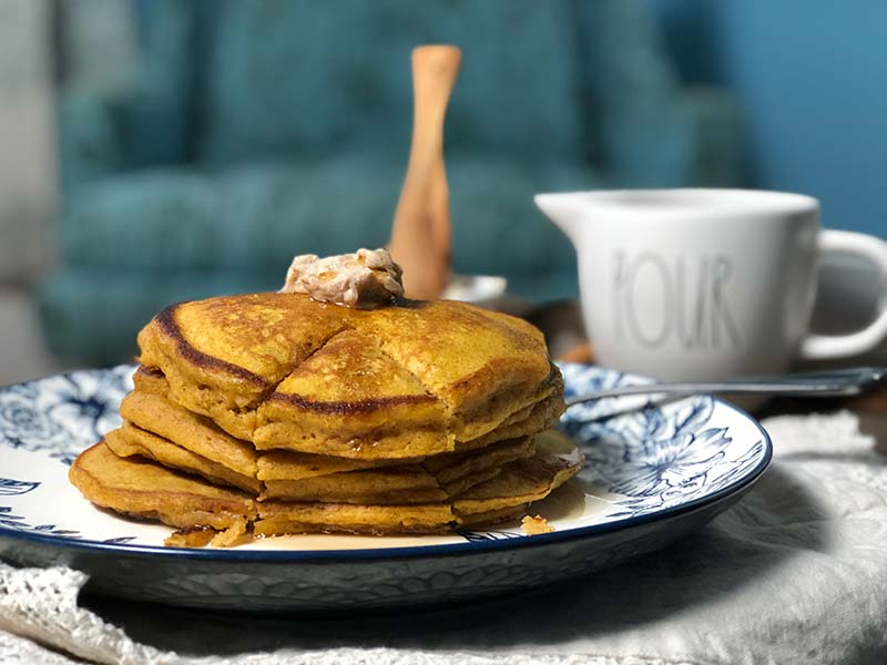 A stack of pumpkin pancakes are cut into for the first time.