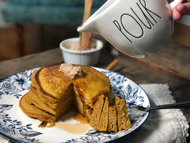 A baker pours real maple syrup over these delicious pumpkin pancakes that are topped with maple cinnamon butter.