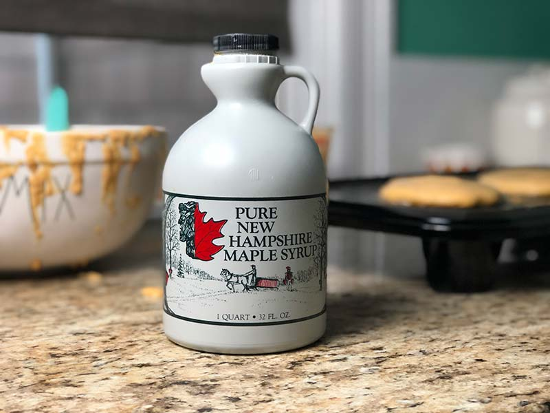 A container of pure New Hampshire maple syrup rests on the counter as the pumpkin pancakes cook in the background.