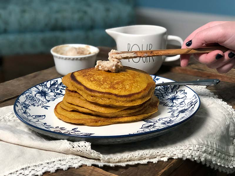 A baker spreads the maple cinnamon butter on a stack of pumpkin pancakes.