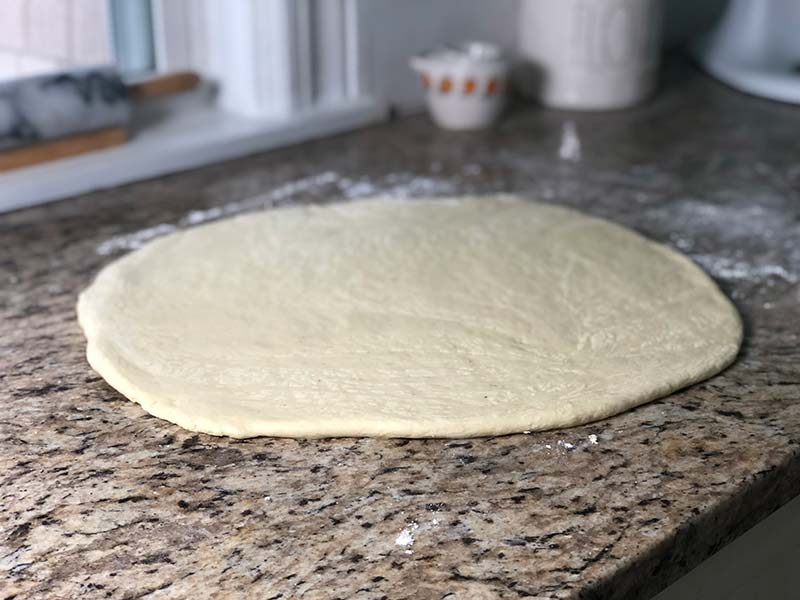 The dough is rolled out before the donuts are cut.