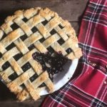 A blueberry raspberry pie, with one piece cut out of it, rests on a table after coming out of the oven.