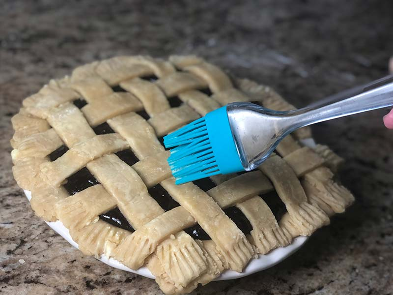 A baker applies the egg wash to the pie crust lattice on the blueberry raspberry pie.