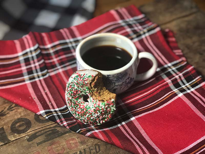 A gingerbread donut with a bite taken out of it rests against a hot cup of coffee.