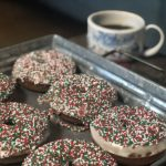 These baked gingerbread donuts with holiday sprinkles are served on a tray with a cup of coffee.