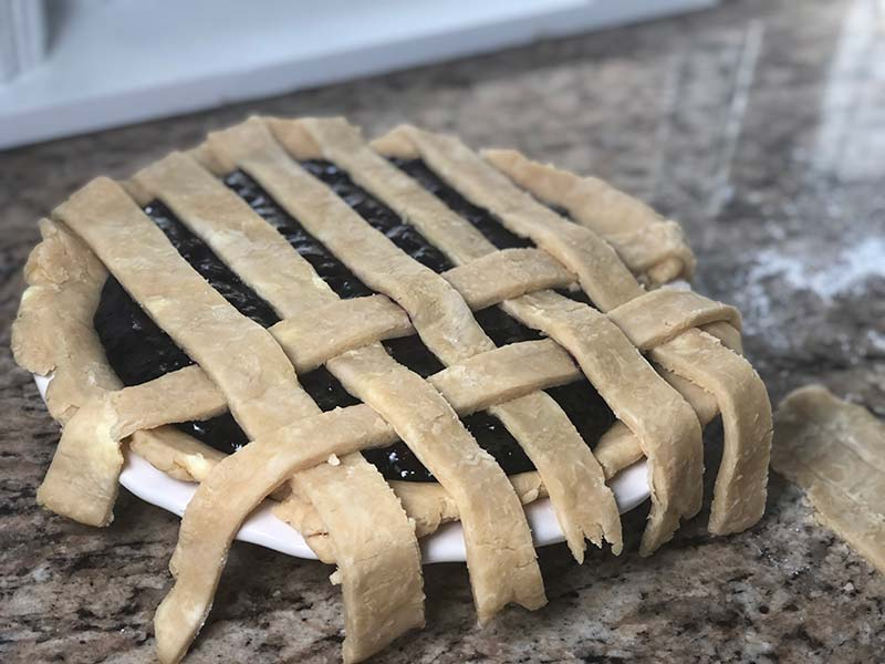 Lattice pie crust is laid on top of the blueberry raspberry pie.