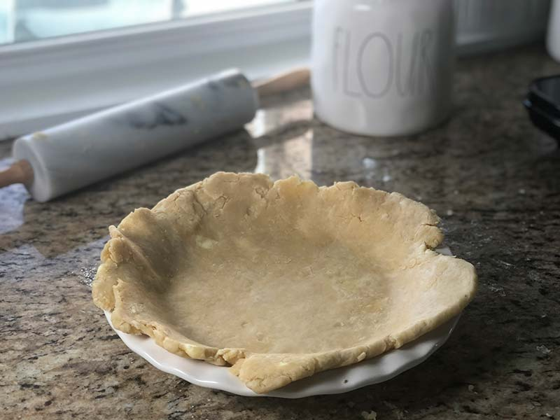 The bottom of the pie crust is draped over the Rae Dunn pie dish for the blueberry raspberry pie recipe.