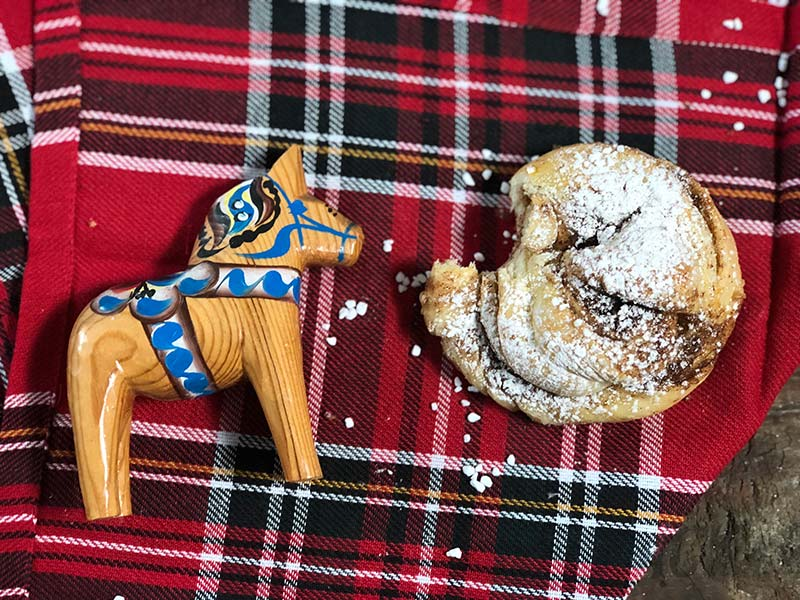 The powdered sugar version of these Swedish cinnamon buns is on display next to a dala horse.