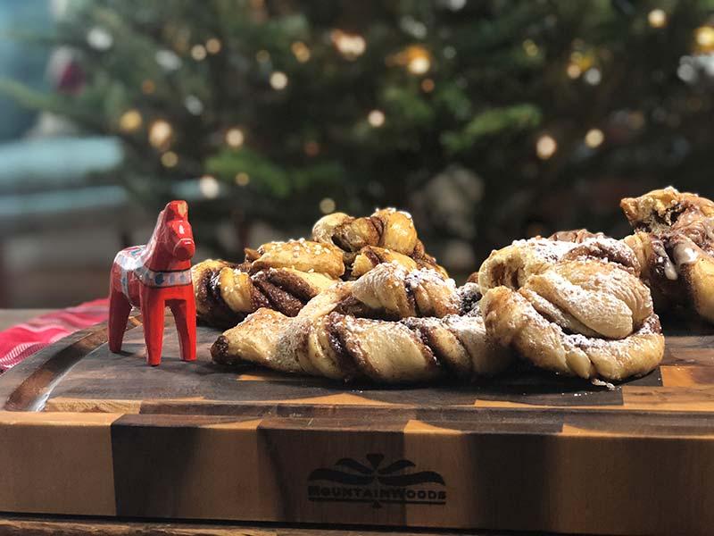 A few Swedish cinnamon buns topped with powdered sugar rest on a cutting board.