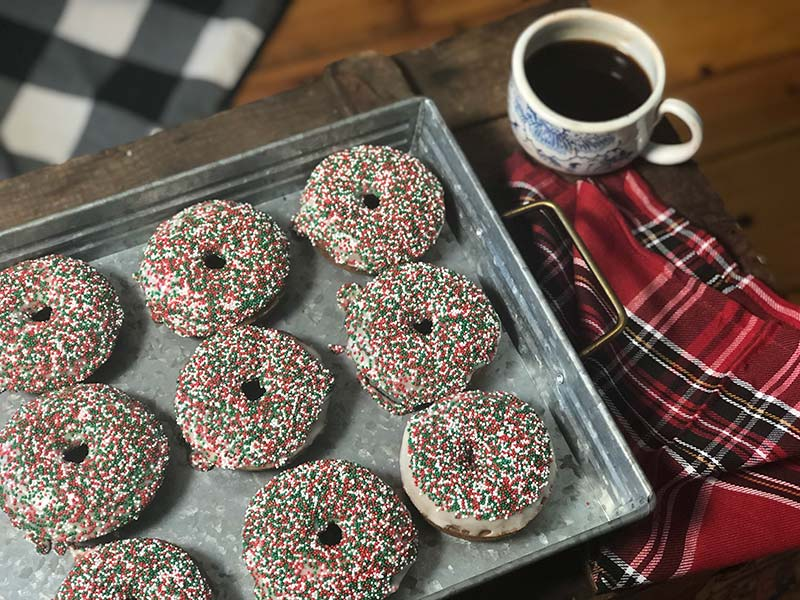 Several baked gingerbread donuts with holiday sprinkles are on display.