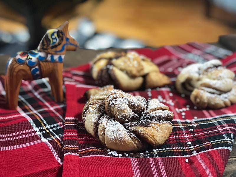 A few Swedish cinnamon buns rest on a cloth napkin.