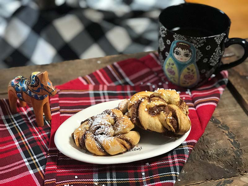 Two Swedish cinnamon buns rest on a plate next to a cup of coffee.