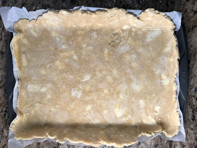 The bottom layer of crust for this giant blueberry Pop-Tart recipe is placed into the baking sheet.