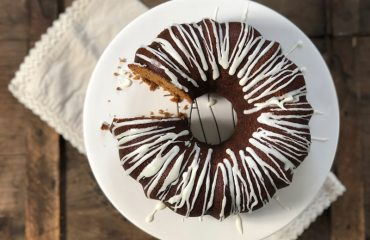 A gingerbread bundt cake with icing is shown on a cake stand for this recipe.