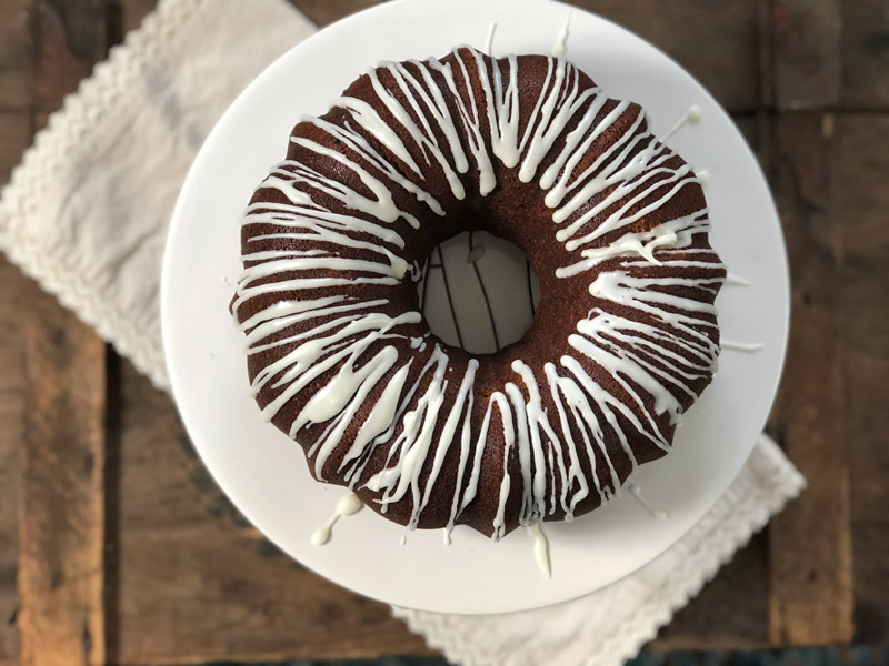 A gingerbread bundt cake with icing is on display for this recipe.