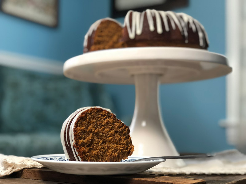 A slice of gingerbread bundt cake is shown on a plate for this recipe.