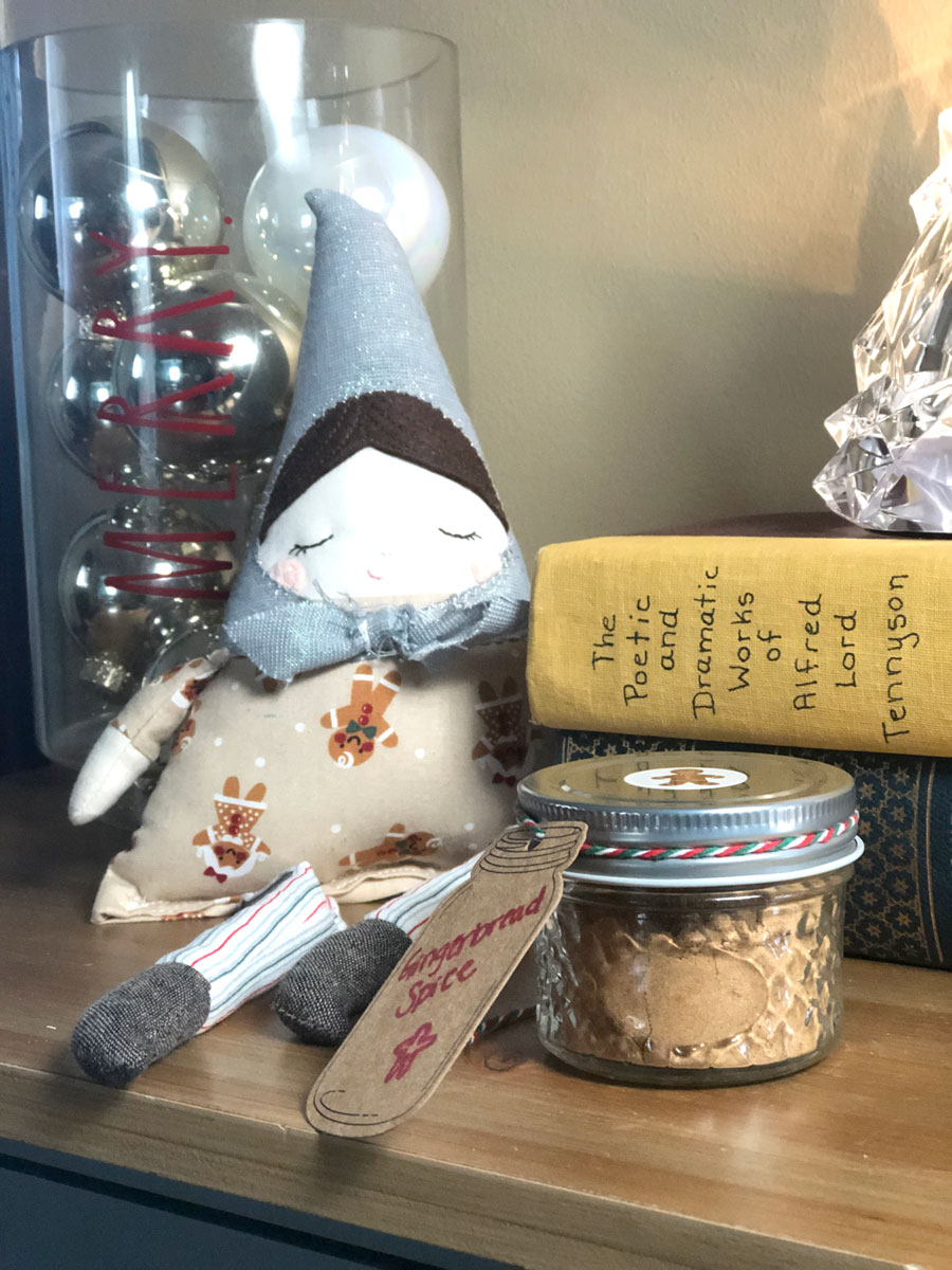 A jar of homemade gingerbread spice mix sits on a counter next to Christmas decorations.