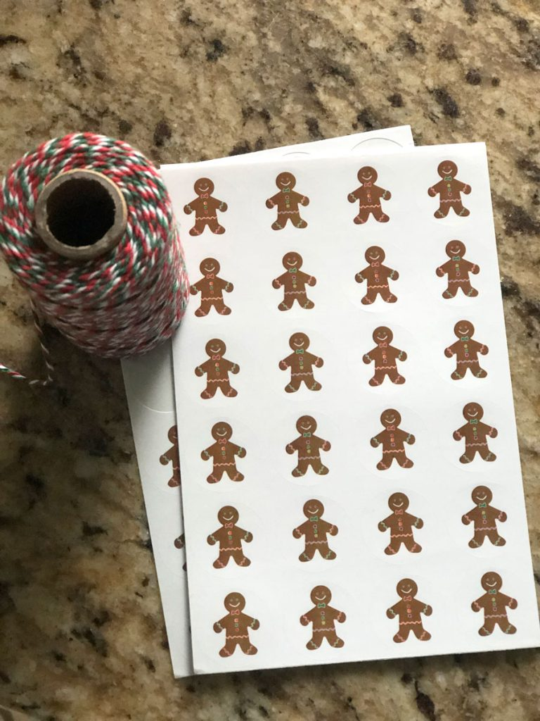 A roll of Christmas twine sits next to a package of Gingerbread stickers, to be used to decorate the gingerbread spice mix jars.