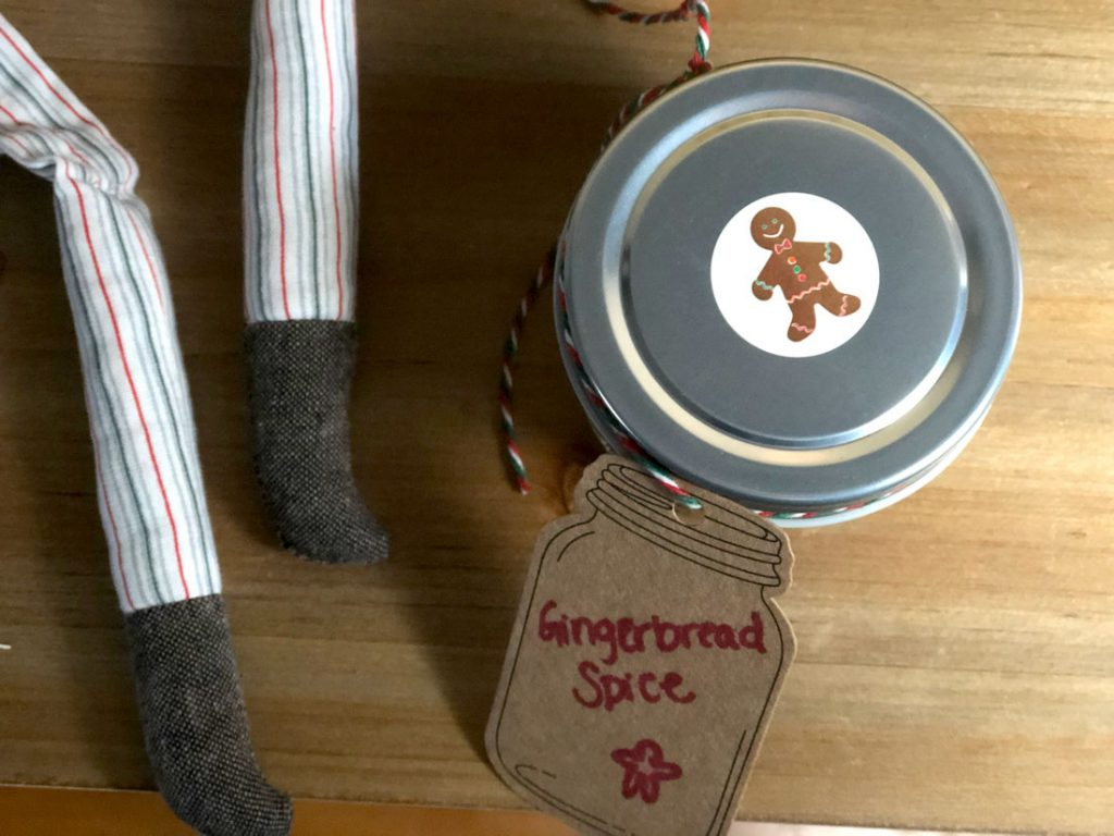 A jar of homemade gingerbread spice mix sits on a table.